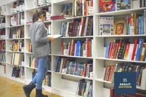kitaplık önünde gri hırkalı ve uzun saçlı kadın