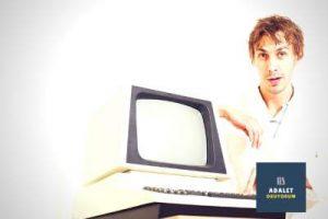 bilgisayar tutan beyaz gömlekli genç adam
