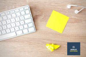 masada beyaz klavye ve sarı not kağıtları