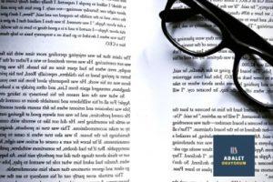 kitap üzerinde siyah çerçeveli gözlük