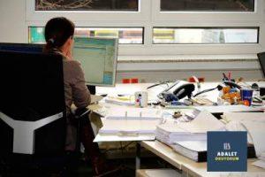 ofis masasında oturan akdın ve masa üstü evraklar