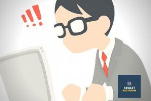bilgisayar ekranına bakan gözlüklü çalışan